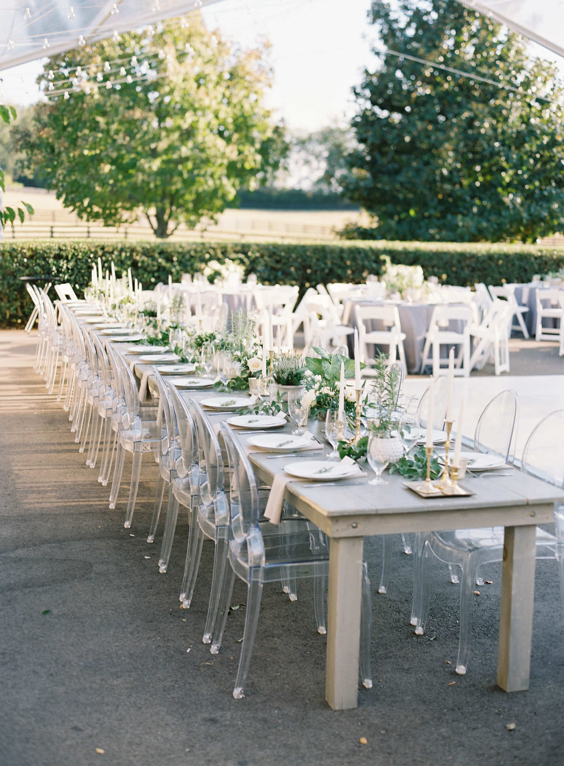 Family style wedding reception tables with greenery