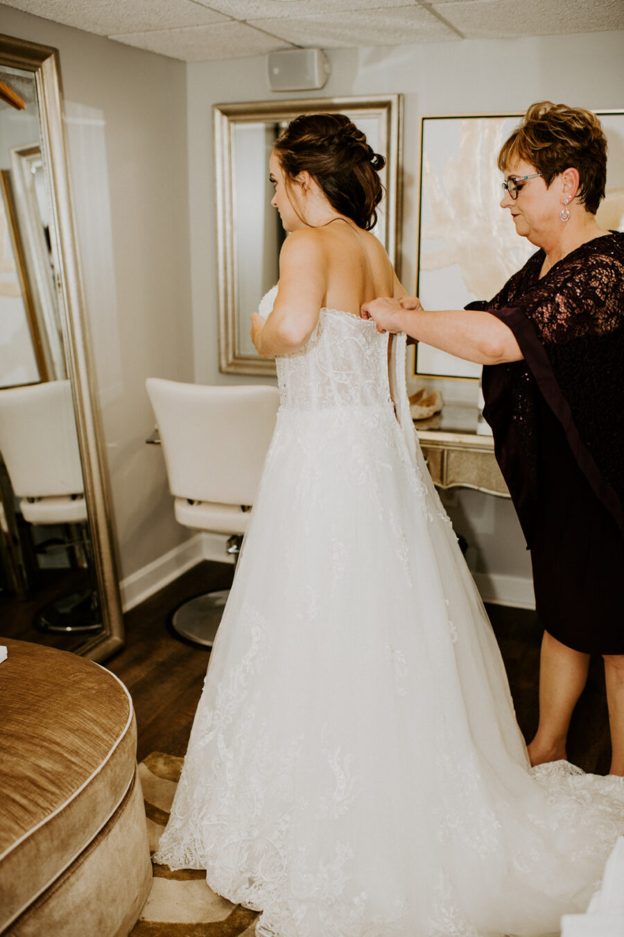 Bride getting ready in wedding dress: Romantic Nashville Wedding at The Bedford featured on Nashville Bride Guide