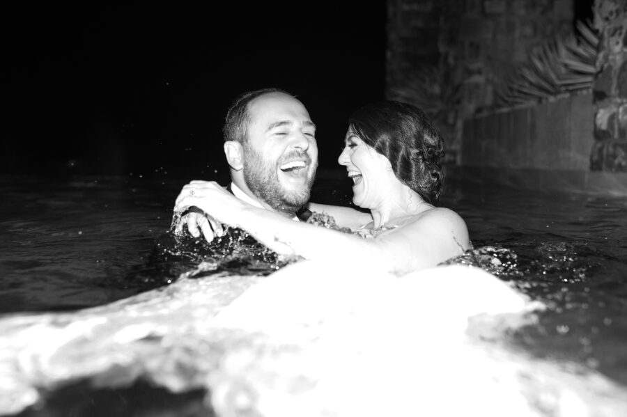 Bride and groom swimming in wedding attire: Intimate Caribbean Wedding by Details Nashville featured on Nashville Bride Guide