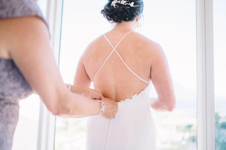 Bride getting ready in wedding dress: Intimate Caribbean Wedding by Details Nashville featured on Nashville Bride Guide