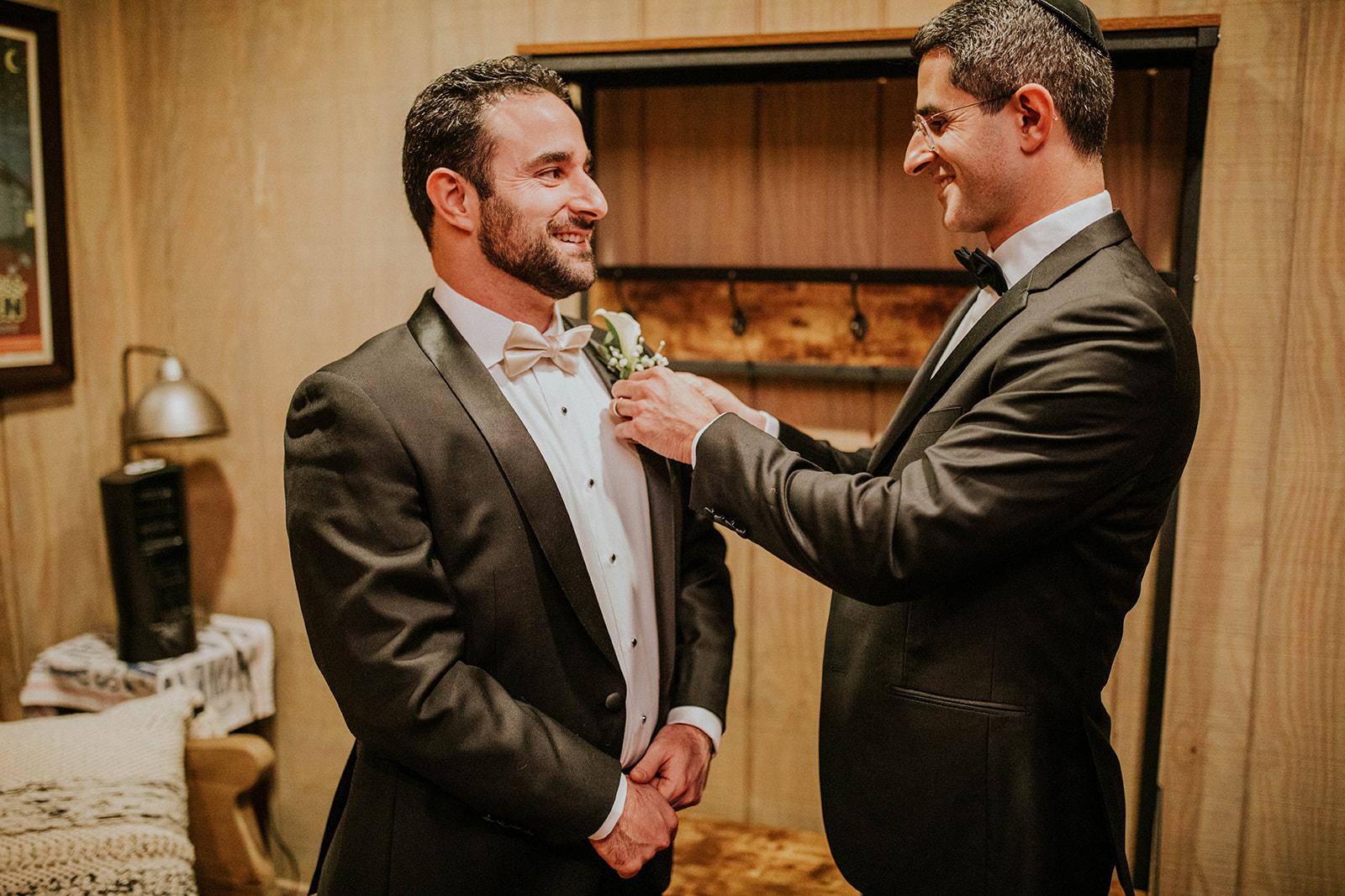 Groomsmen fixing grooms wedding boutonniere