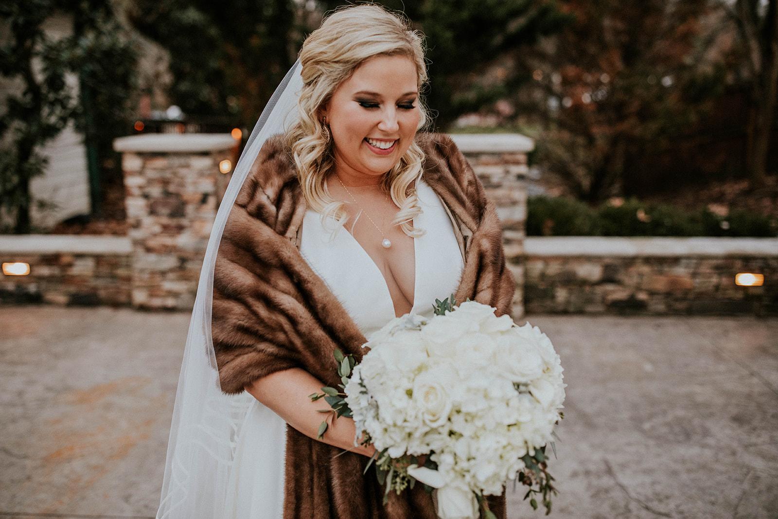 White bridal bouquet and faux fur shawl