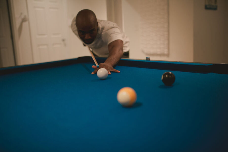 Groom playing pool the morning of his wedding: Romantic Outdoor Wedding at Reunion Stay