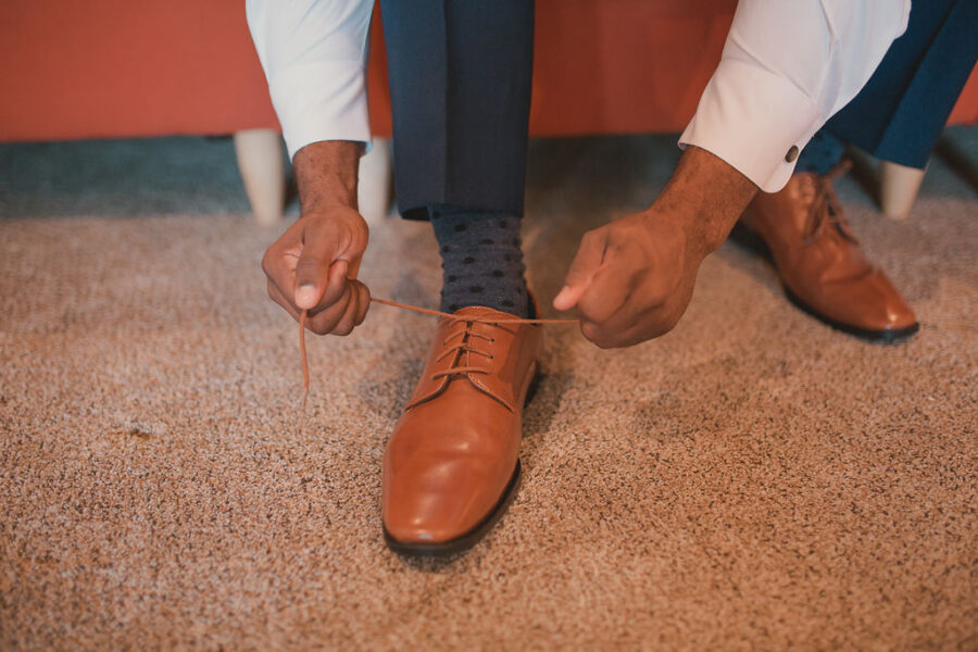 Groom tying shoes: Romantic Outdoor Wedding at Reunion Stay