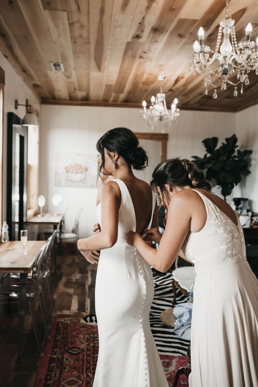 bridesmaid helping bride get into wedding dress