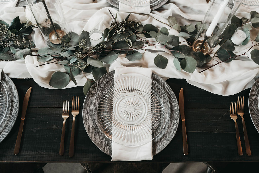 wedding place setting with clear plates and white linens