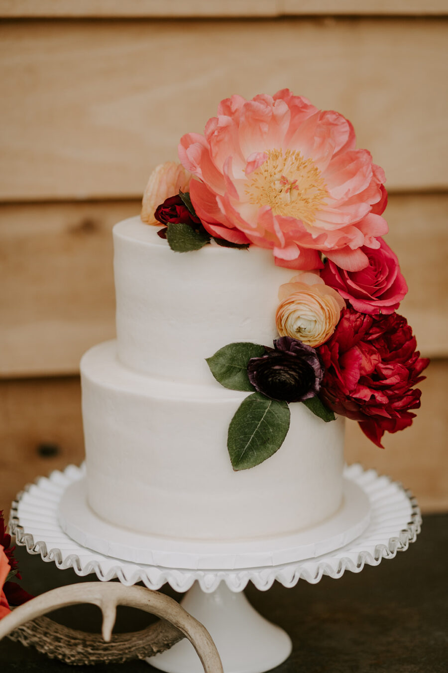 White wedding cake with pink and red flowers