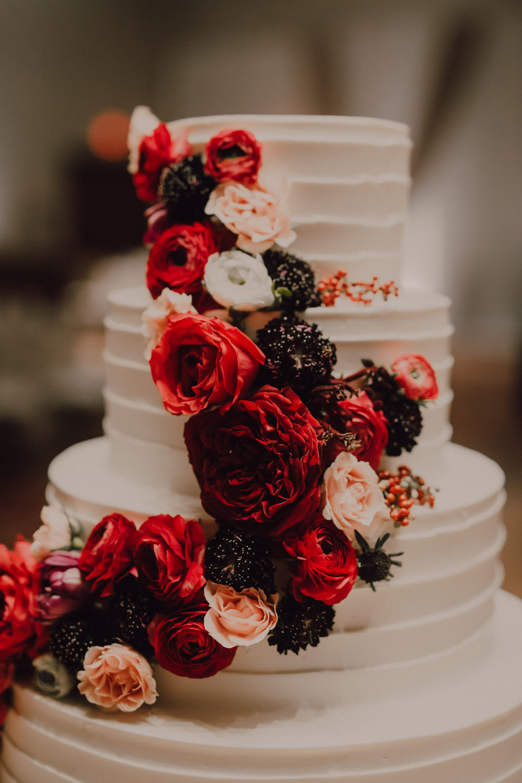 White wedding cake with cascading red flowers | Nashville Bride Guide
