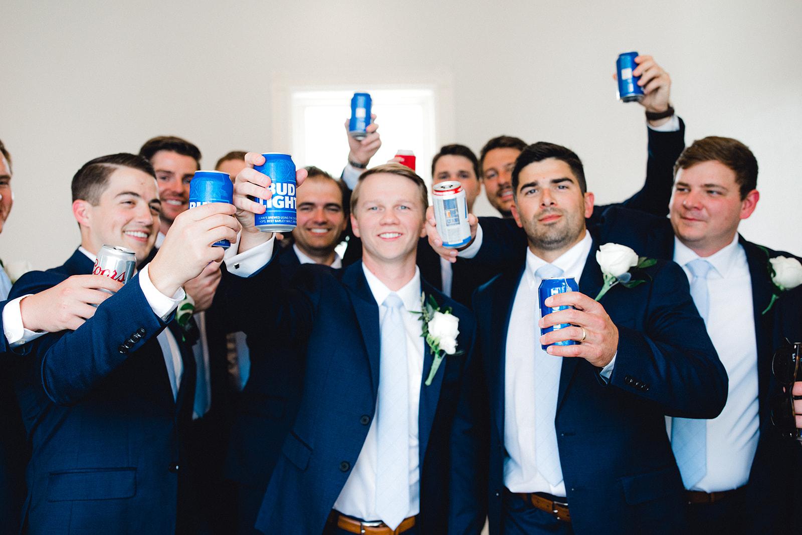 Groom and groomsmen cheers with beer