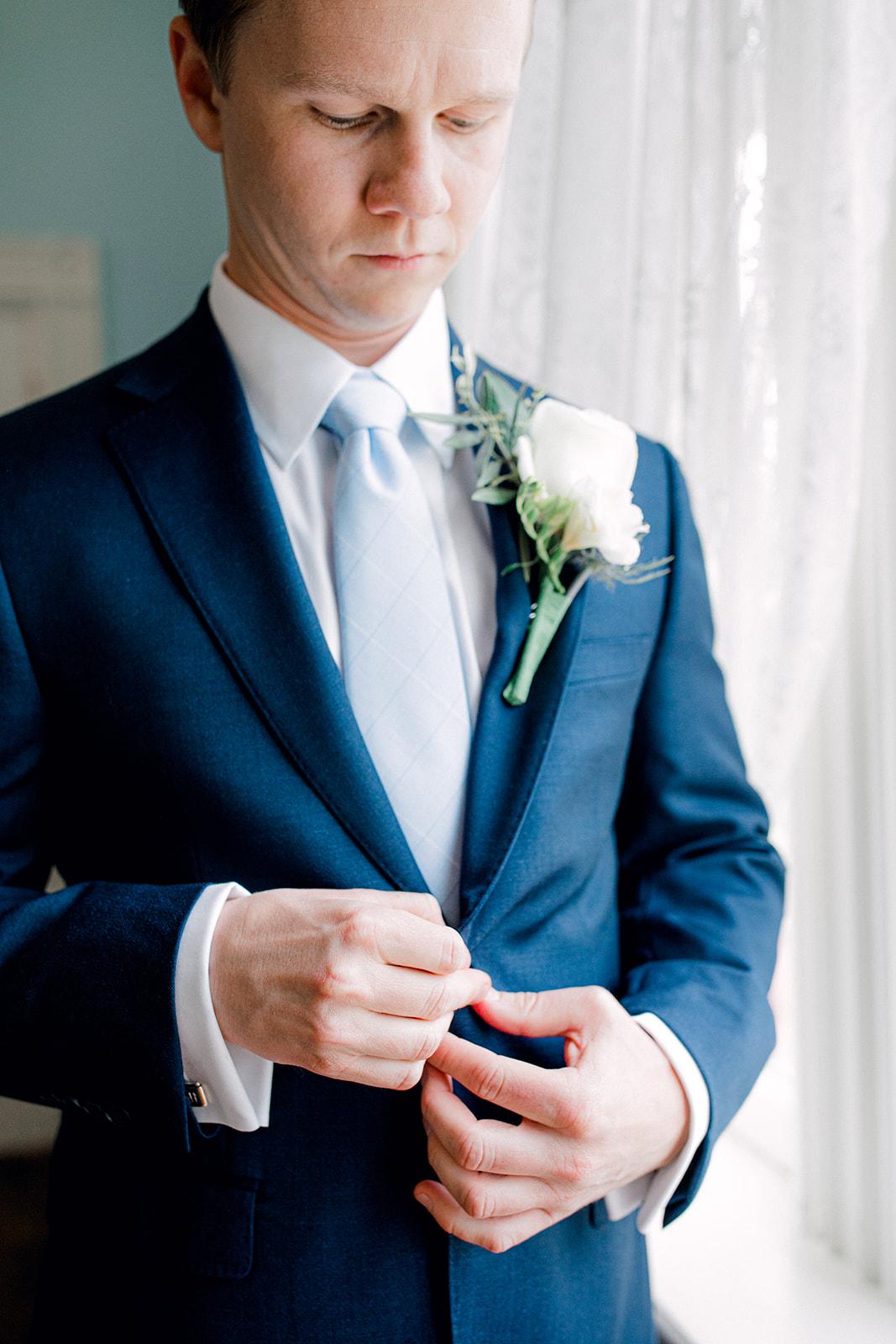 Blue wedding tuxedo with white wedding boutonniere