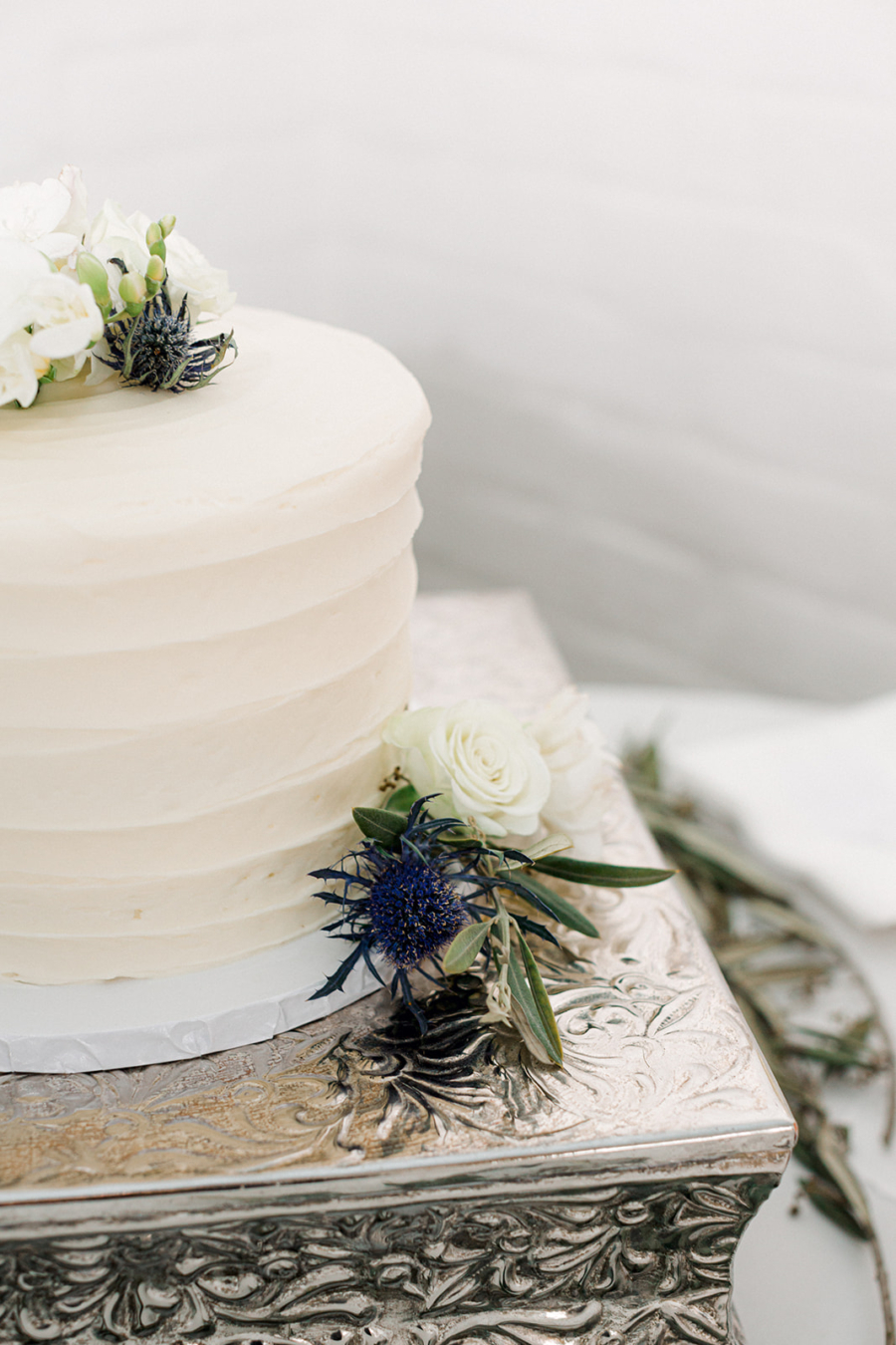 Simple white wedding cake with blue thistle flowers