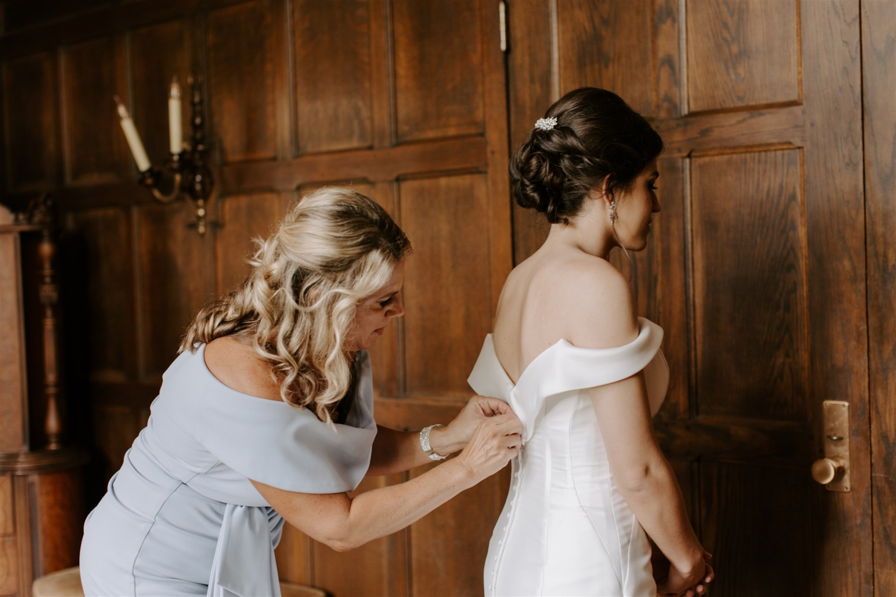 Mother helping bride with off the shoulder wedding dress