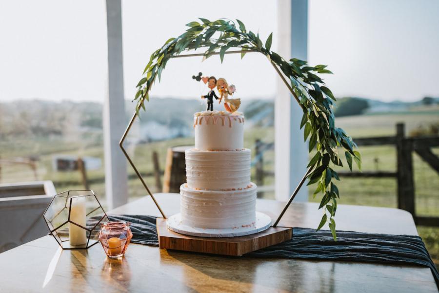 White wedding cake with geometric cake stand
